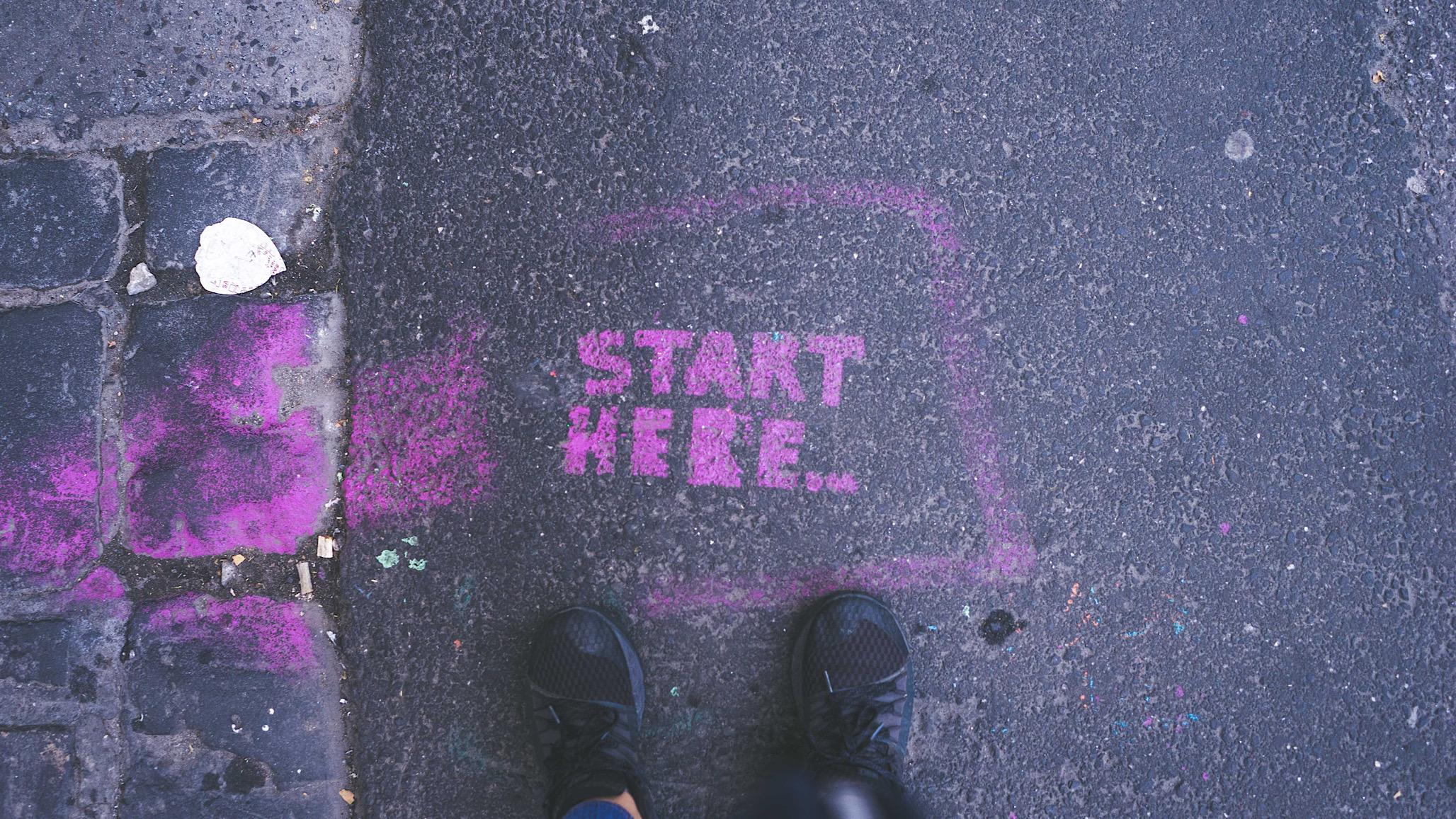 """Graffito su asfalto con scritto """"start here"""""""
