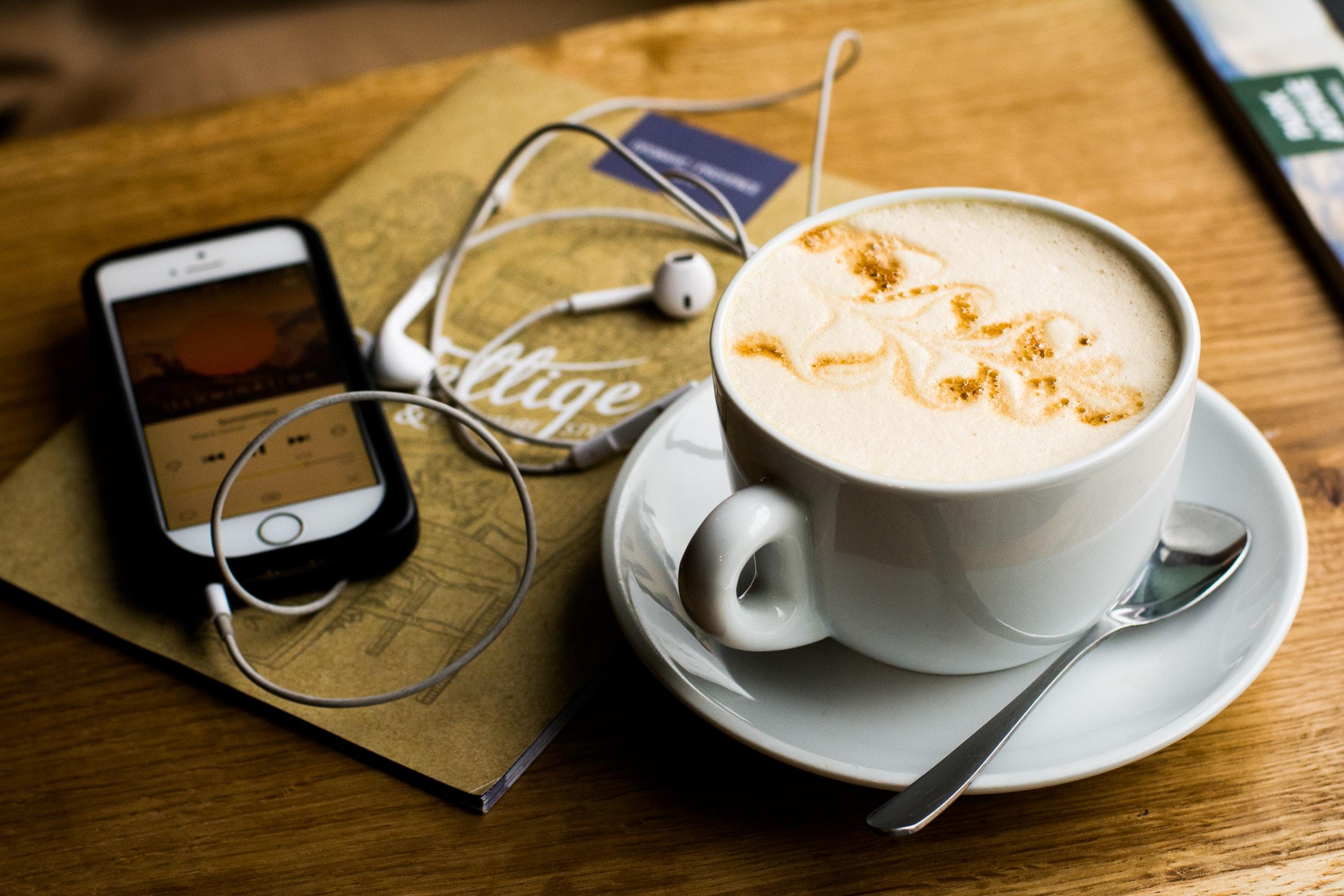Uno smartphone su cui è in ascolto un podcast, accanto a un cappuccino