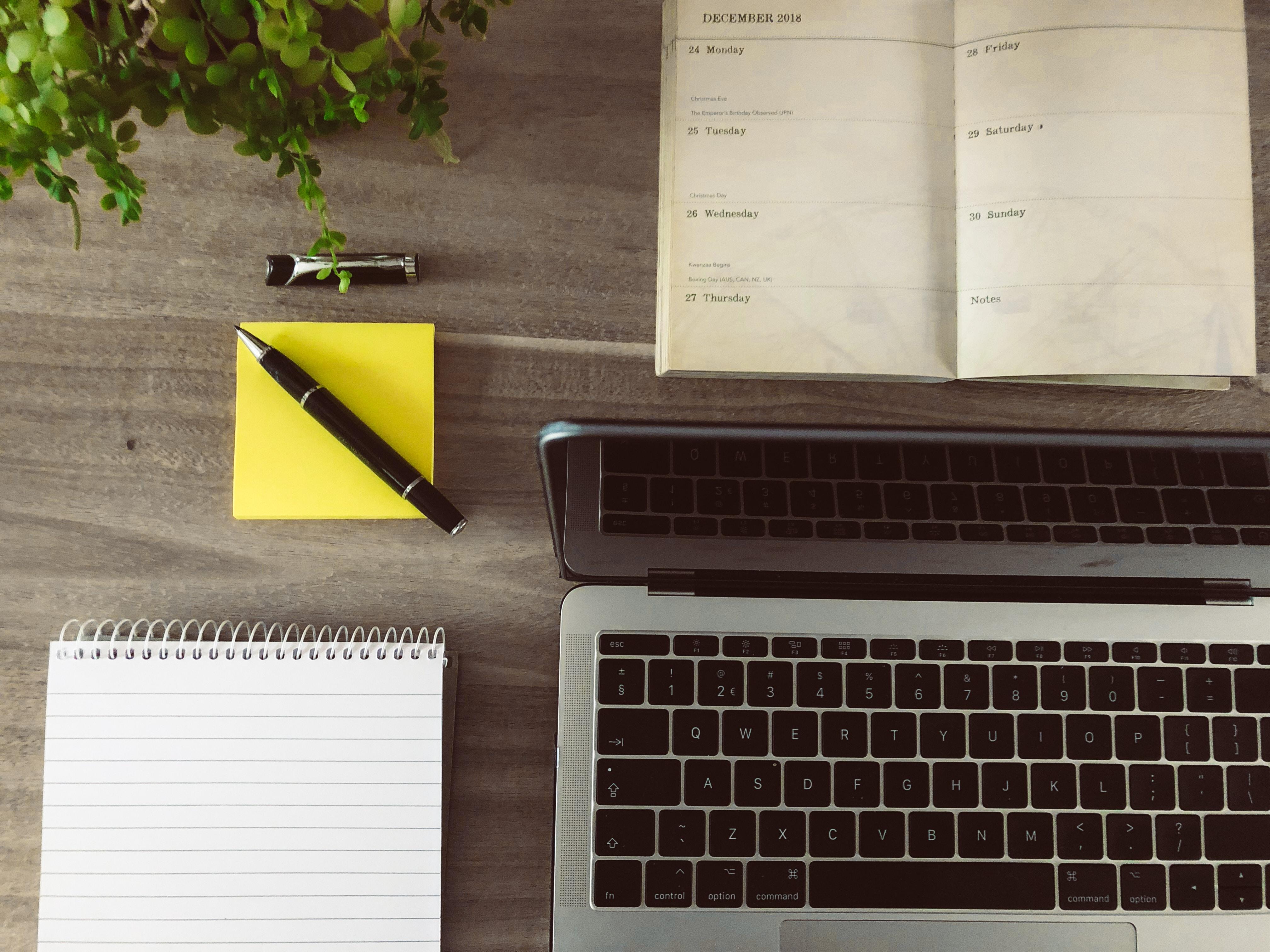 Un portatile e delle agende su un tavolo